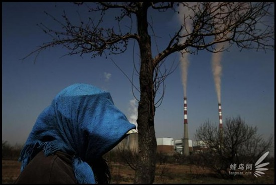 Shizuishan Industrial district in Ningxia province (宁夏石嘴山湖滨工业园区), the tall chimneys spitted out smoke and dust. Residents took preventive measure for the falling dust from the sky when going outside. April 22, 2006