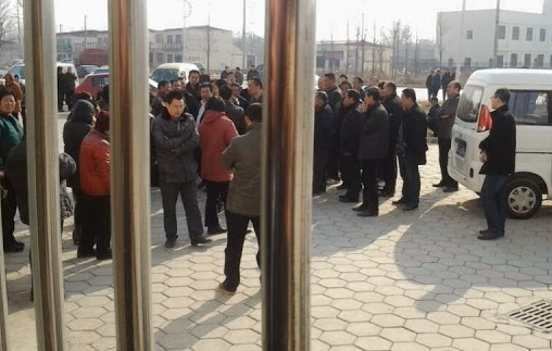 Photo of mob, taken by reporters hiding in an office. Photo via China Aid.